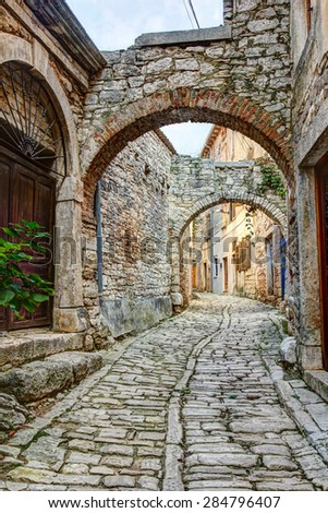 A typical narrow street or alley with stone houses in the hilltop town of Bale or Valle in Istria, Croatia. - stock photo