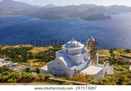 A typical view of the Greek Islands - Greek Orthodox Church white on the mountain against the sea, Plaka village, Milos island, Cyclades, Greece. - stock photo