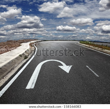 A U turn arrow traffic symbol imprint on a lonely asphalt road against a blue cloudy sky.  - stock photo