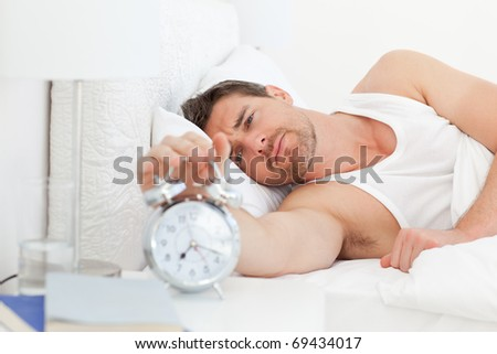 A unhappy man in his bed before waking up in his bedroom - stock photo