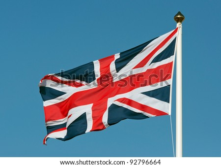 A union jack flag flying in a clear blue sky showing movement from the wind. - stock photo