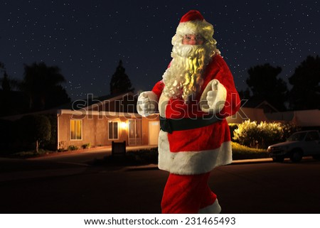 A unique and Rare Shot of Santa Claus, yes SANTA CLAUS as he walks in front of a house and gives you the Thumbs Up sign. Even Santa Claus needs exercise and walks around neighborhoods at night.  - stock photo