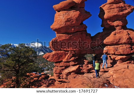 "A Unique giant rock formation in the Garden of the Gods at Colorado Springs Colorado which is nick-named ""Siamese Twins"". Snow-capped Pikes Peak can be seen in the background along with tourists - stock photo"