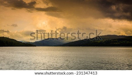 A unique moody/stormy view across Lake Windermere on the edge of a dark storm with dark/contrasting lighting - stock photo