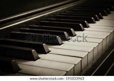 A unique perspective of piano keys on an old piano; sepia colortone - stock photo