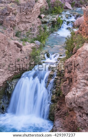 A unnamed waterfall cuts through Havasu Canyon on the Havasupai Indian Reservation in the Grand Canyon. - stock photo