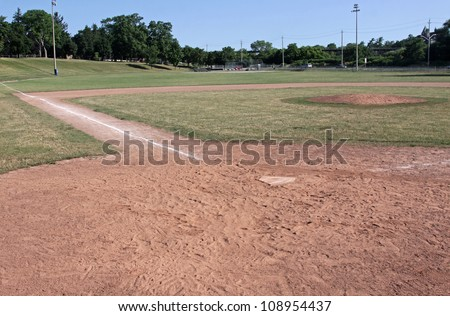 A unoccupied baseball field, shot from behind home plate. - stock photo