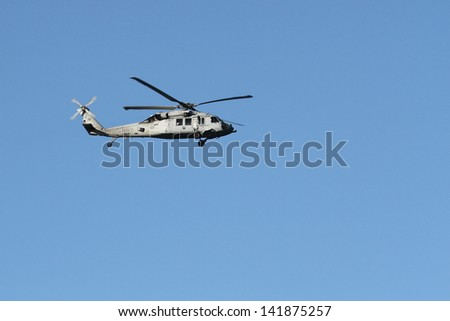 A US Navy HH-60H Seahawk flying from left to right - stock photo