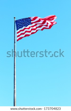 A USA flag flies in a strong wind  - stock photo