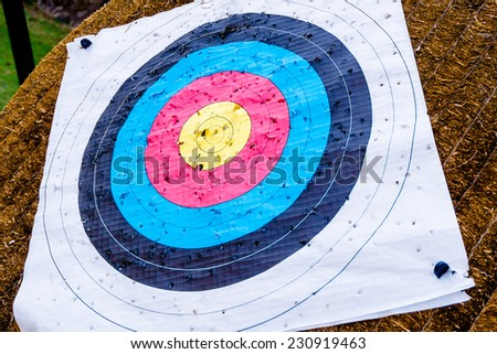 A used archery target full of holes applied to a straw mount - stock photo