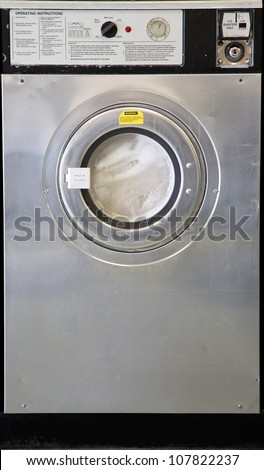 a used industrial washing machine with clothes inside being washed - stock photo