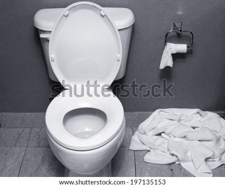 A used towel dropped on the floor next to a toilet. - stock photo