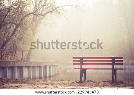 A vacant riverside bench on a foggy morning - stock photo