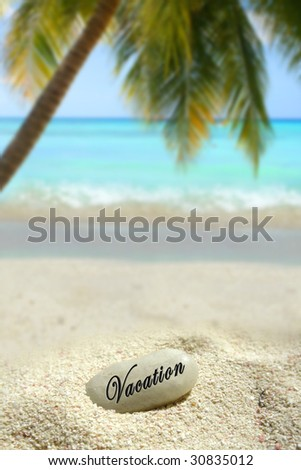 a vacatiion stone in the sand on a tropical beach - stock photo