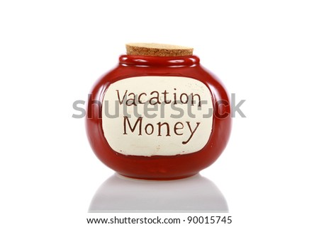 a vacation money jar, filled with cash for future vacations, holidays, weekend getaways, quick jaunts, driving trips, world travel, and any other excuse to get away and be free of concerns - stock photo