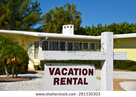 A Vacation Rental Sign in front of a yellow one story home on the beach.  - stock photo