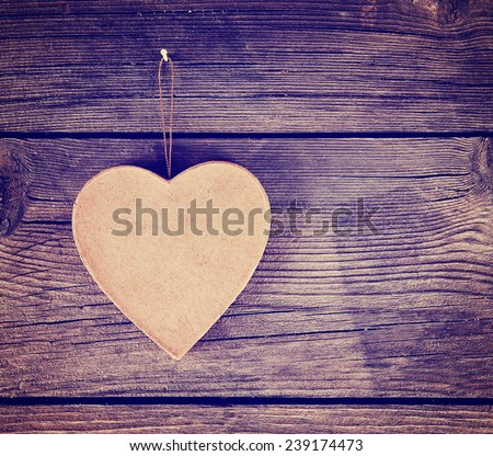 a valentine's day heart on a wooden background toned with a retro vintage instagram filter effect - stock photo