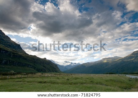 A valley in New Zealand with view on a glacier in the background - stock photo
