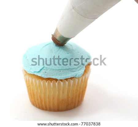 A vanilla cupcake with blue frosting being decorated - stock photo