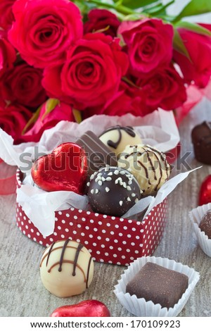 A variety chocolates and truffles on a grey background - stock photo