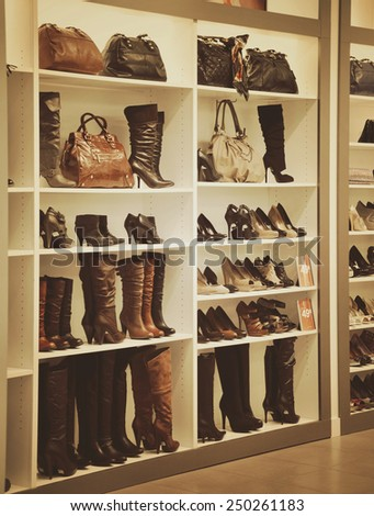 A variety of boots and purses are on display at a store on white shelves for sale. Use it for a shopping or fashion concept. - stock photo
