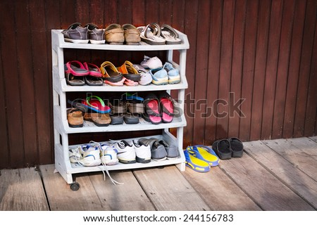 A variety of colorful shoes, neatly ordered on a plastic shoe rack outside a wooden house. - stock photo