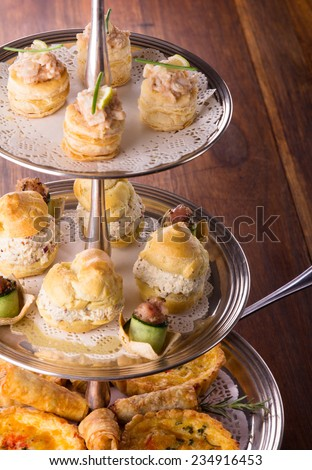 A variety of delicious savory pastries and bites served on a silver cake stand. The selection includes quiches, spring rolls, scones with chicken and seafood. - stock photo