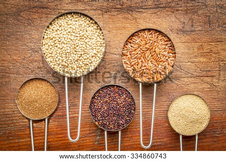 a variety of gluten free grains (from left: teff, sorghum, black quinoa, brown rice, and amaranth)  - set of metal measuring cups isolated against rustic wood - stock photo