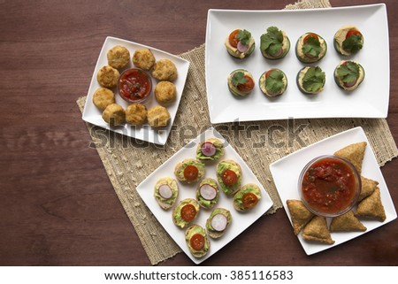 A variety of healthy tapas including avocado toast, samosas and cucumber hummus bites. - stock photo