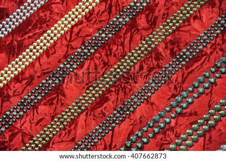 A variety of metal chains of balls on red suede background, background, texture,  - stock photo