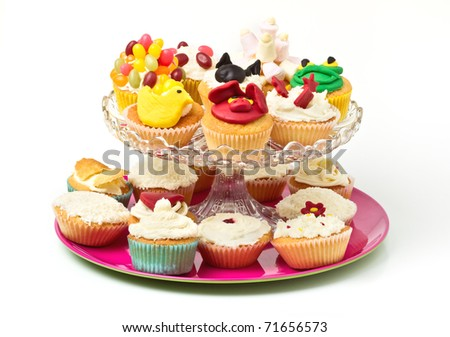 A variety of vibrant fun homemade cup cakes on cake stand. - stock photo