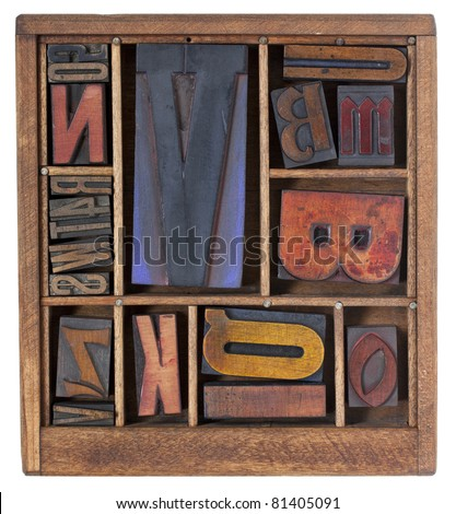 a variety of vintage letterpress printing blocks with big letter V in a small wooden typesetter box with dividers, isolated on white - stock photo