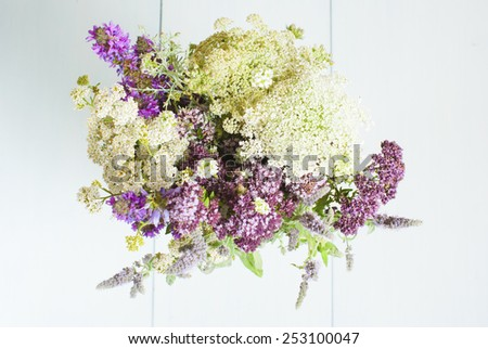 a vase of wildflowers on white wooden table - stock photo