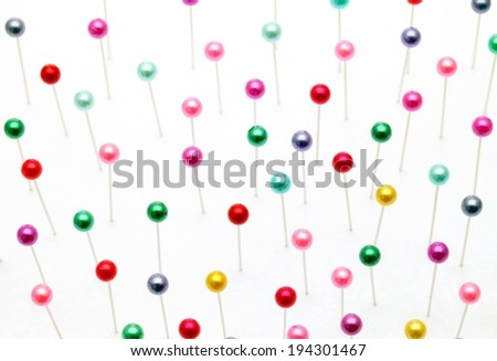 A vast amount of colorful push pins on a white surface. - stock photo