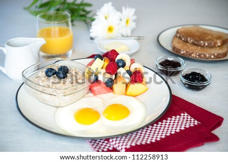 A vegetarian beautiful breakfast plate meal with eggs sunny side up, fresh mixed fruit, hot oatmeal, orange juice and wheat toast. - stock photo