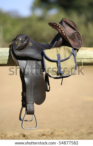 A vertical photograph of horse riding tack, including saddle, bag and leather hat - stock photo