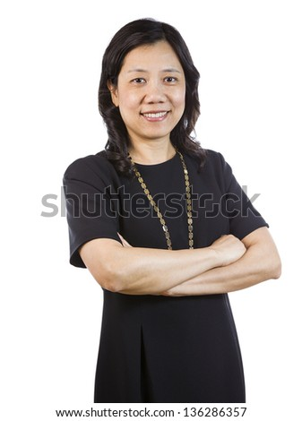 A vertical portrait photo of a mature Asian woman wearing a dark dress with arms crossed while smiling on white background - stock photo