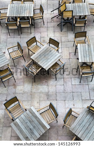 A vertical shoot of a outdoor restaurant with wooden furniture have not open for business yet. - stock photo