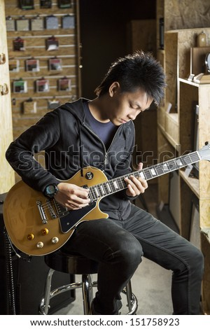 A vertical shot of a young asian man playing electric guitar. - stock photo