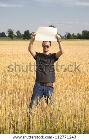 A vertical view of a young farmer standing in his field of wheat holding a blank sign. - stock photo