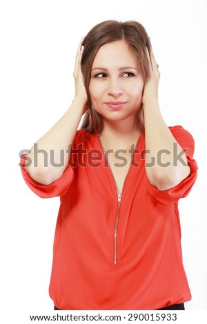 A very angry and frustrated woman covering her ears. Isolated on white. - stock photo