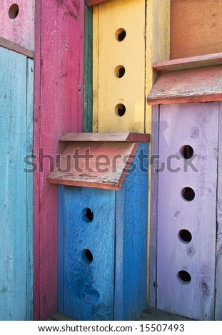 A very colorful birdhouse with colors in vivid paint colors for each section. This is a single structure with multiple holes that allow it to support a flock of birds. - stock photo