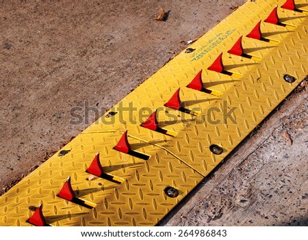 a very dangerous car direction control equipment in yellow and red with sharp metal steel pins in raw installed on the floor on the exit way to prevent car drive in from the wrong way in THAILAND - stock photo
