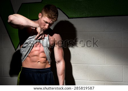 A very fit man showing off his abs in dramatic fashion. I used dramatic lighting to get the sense of focus, and determination, and motivation down.  - stock photo