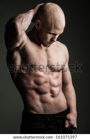 a very fit shirtless young man flexing hs muscles - stock photo
