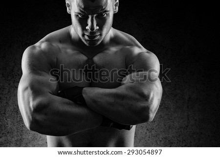 a very fit young male flexing his muscles - stock photo