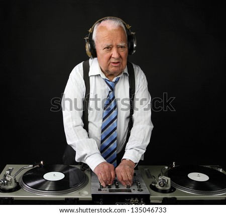 a very funky elderly grandpa dj mixing records - stock photo