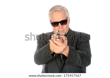 A very good looking well dressed business man in a suit brandishes a small pistol while wearing dark sunglasses. Isolated on white with room for your text. He could be a CIA Mole or Mob Lackey.  - stock photo