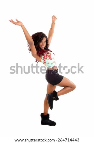 A very happy African American young woman in black shorts and boots