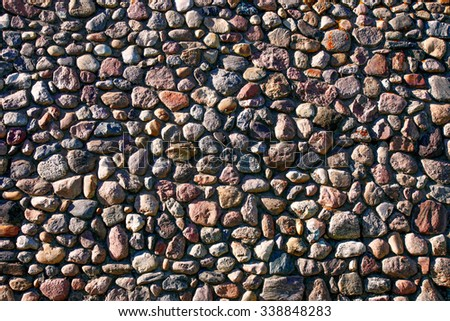 A very large wall of many different rocks and stones illuminated by sunlight. - stock photo